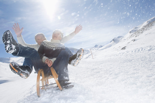 Senior couple sledding in mountainsの写真素材 [FYI02118344]