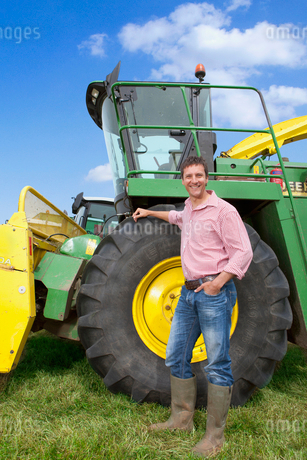 Portrait of smiling farmer leaning on tractorの写真素材 [FYI02118347]