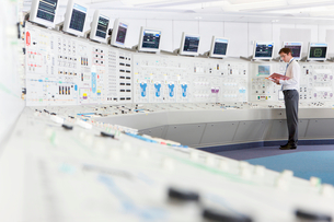 Engineer with binder at control panel in control room of nuclear power stationの写真素材 [FYI02118350]