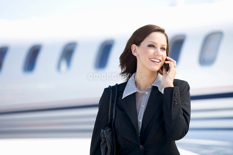 A business woman talking on a mobile phone next to a planeの写真素材 [FYI02118355]