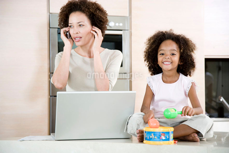 Stressed mother working from home while daughter plays a toy drumの写真素材 [FYI02118360]