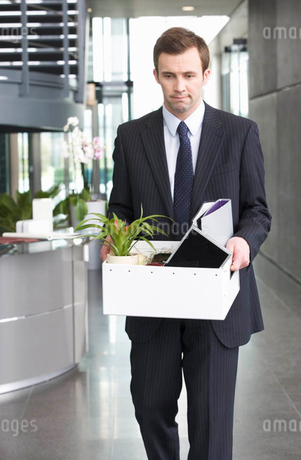 A redundant businessman taking his belongings home in a boxの写真素材 [FYI02118371]