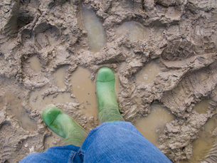 Person in rubber boots standing in mudの写真素材 [FYI02118372]