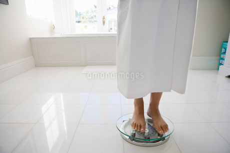 Young woman wearing white bath robe, standing on weighing scales, low sectionの写真素材 [FYI02118407]