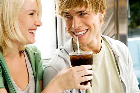 Young couple sharing a cola drink in a dinerの写真素材 [FYI02118428]