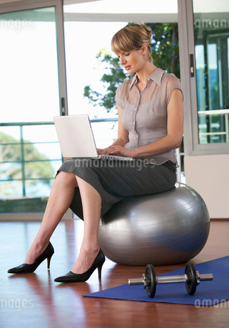 A businesswoman sitting in a gym using a laptopの写真素材 [FYI02118429]