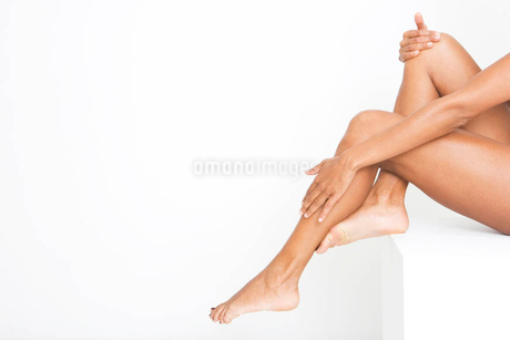 A woman applying moisturiser to her feetの写真素材 [FYI02118458]