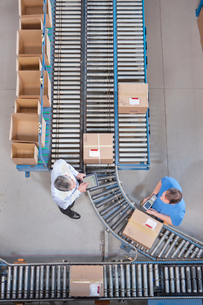 Businessman with digital tablet and worker packing box at conveyor belt in distribution warehouseの写真素材 [FYI02118467]