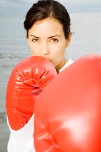 A woman wearing boxing gloves on a beachの写真素材 [FYI02118485]