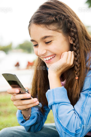 A young girl using a mobile phoneの写真素材 [FYI02118497]