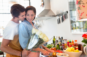 Man surprising woman in kitchen with bouquet of flowersの写真素材 [FYI02118503]