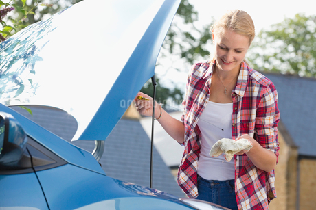 Woman Checking Oil Level In Car Engineの写真素材 [FYI02118512]