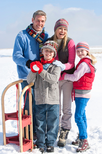Portrait of smiling family with snowball and sled in snowの写真素材 [FYI02118513]
