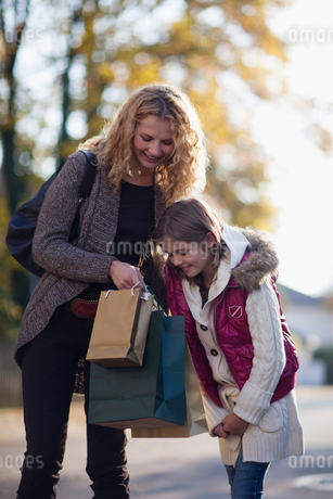 A mother and daughter looking in their shopping bagsの写真素材 [FYI02118518]