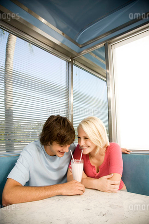 Portrait of a teenage couple sharing a milkshake in a dinerの写真素材 [FYI02118521]