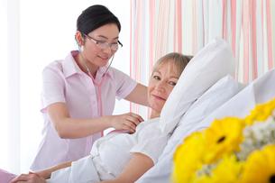 Nurse listening to patient's heartbeat in hospital roomの写真素材 [FYI02118530]