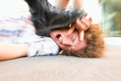 Young man lying on ground being stepped on by someone wearing black bootの写真素材 [FYI02118542]