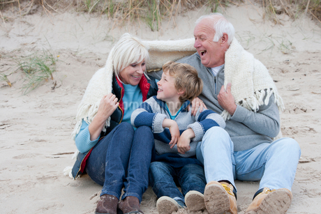 Grandparents And Grandson Sheltering Under Blanket On Beachの写真素材 [FYI02118543]
