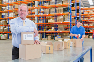 Portrait of smiling supervisor leaning on box on production line in distribution warehouseの写真素材 [FYI02118580]