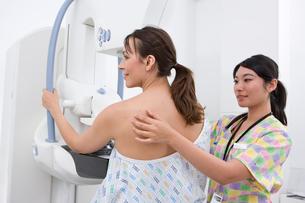 Radiologist helping patient with mammogramの写真素材 [FYI02118625]