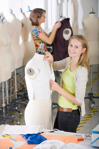 Fashion design student working on garment on mannequinの写真素材 [FYI02118626]