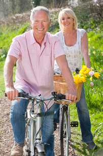 Portrait of smiling senior couple on bicycles with spring flowers in basketの写真素材 [FYI02118673]