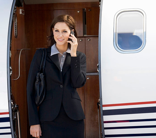 A business woman talking on a mobile phone next to a planeの写真素材 [FYI02118696]
