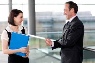 Male and female business colleagues chatting in office buildingの写真素材 [FYI02118703]