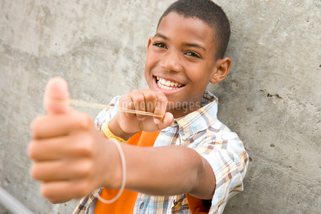 Teenage boy (13-15) preparing to flick rubber band, smiling, portraitの写真素材 [FYI02118725]