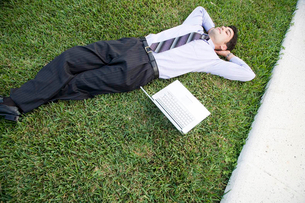 A businessman laying in a park with his laptopの写真素材 [FYI02118750]