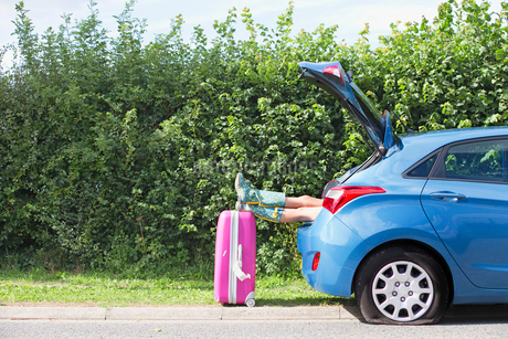 Woman With Flat Tyre On Car Resting Feet On Suitcaseの写真素材 [FYI02118761]
