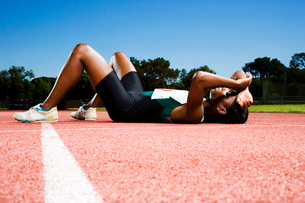 Female athlete resting on a running trackの写真素材 [FYI02118770]