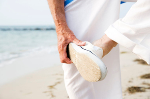 Close up of a senior man putting on his shoes on a beachの写真素材 [FYI02118774]