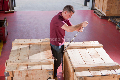 Worker opening crate with crowbar in warehouseの写真素材 [FYI02118823]