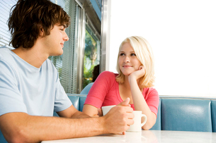 Portrait of a teenage couple flirting in a dinerの写真素材 [FYI02118824]