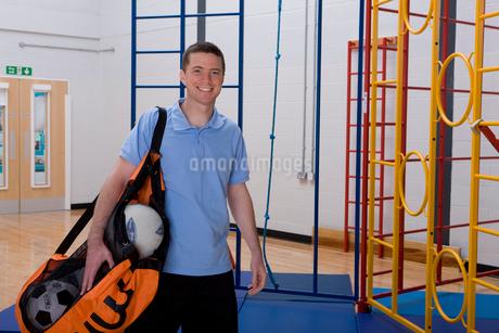 Gym teacher carrying bag of balls in school gymnasiumの写真素材 [FYI02118829]