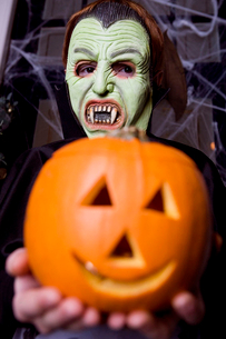Child in a Count Dracula costume at Hallowe'en, holding a pumpkin with a carved faceの写真素材 [FYI02118831]