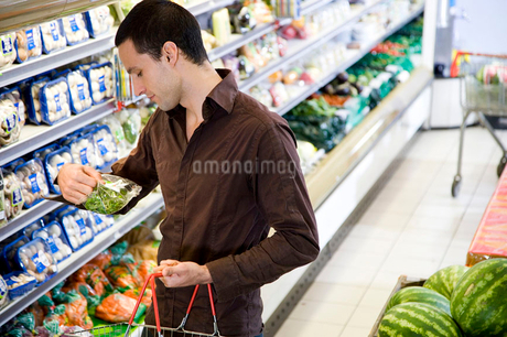 Man reading the label on food packaging in a supermarketの写真素材 [FYI02118848]