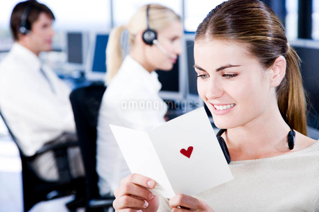 Businesswoman reading her valentines card in an officeの写真素材 [FYI02118858]