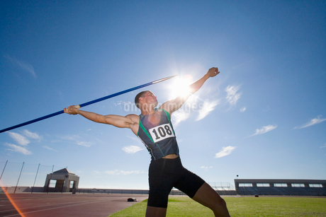 Male athlete preparing to throw javelin, low angle view (lens flare)の写真素材 [FYI02118865]