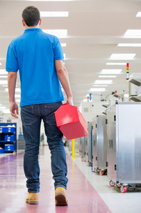 Repairman holding toolbox in aisle of manufacturing plantの写真素材 [FYI02118873]
