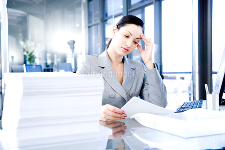 Businesswoman looking stressed with her paperworkの写真素材 [FYI02118886]