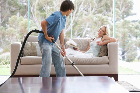 A young boy vacuuming whilst his mother relaxesの写真素材 [FYI02118887]