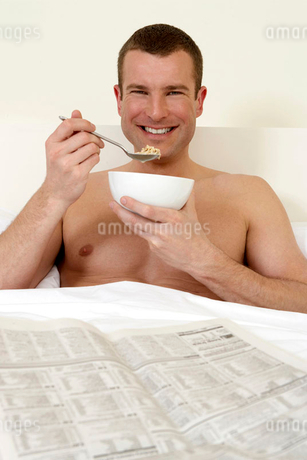 Young man in bed eating breakfast and reading the papersの写真素材 [FYI02118888]
