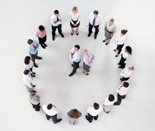 Portrait of businessman and businesswoman standing back to back in circle formed by co-workersの写真素材 [FYI02118917]