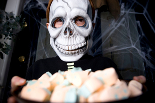Boy in a skeleton costume at a Hallowe'en party, holding a tray of sweetsの写真素材 [FYI02118980]