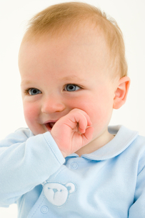 Baby boy (3-6 months) with hand to mouth smilingの写真素材 [FYI02119014]