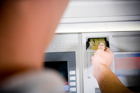 Close up of a young woman using a cashpoint or ATMの写真素材 [FYI02119035]