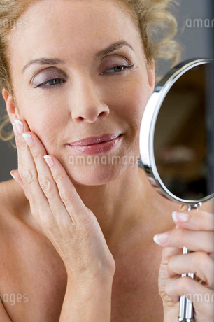 A middle-aged woman looking at her face in the mirrorの写真素材 [FYI02119048]