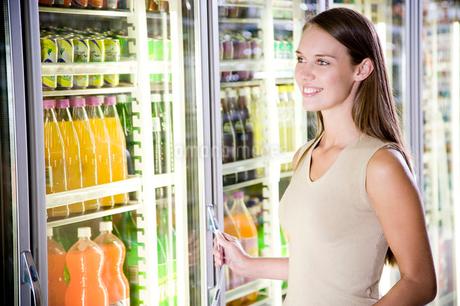 Woman opening a refrigerator door in a supermarketの写真素材 [FYI02119089]